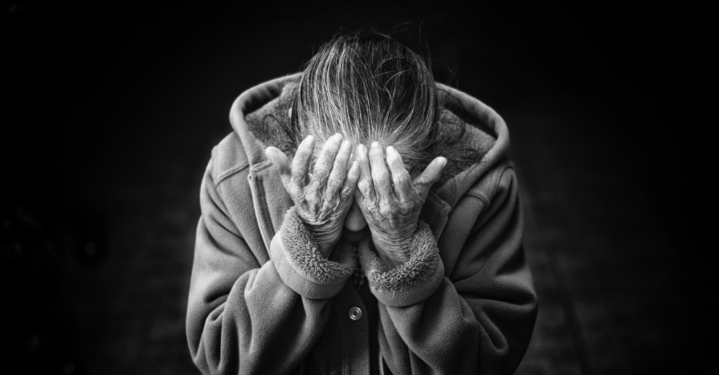 An old woman has lowered her head and has covered her eyes with her palms