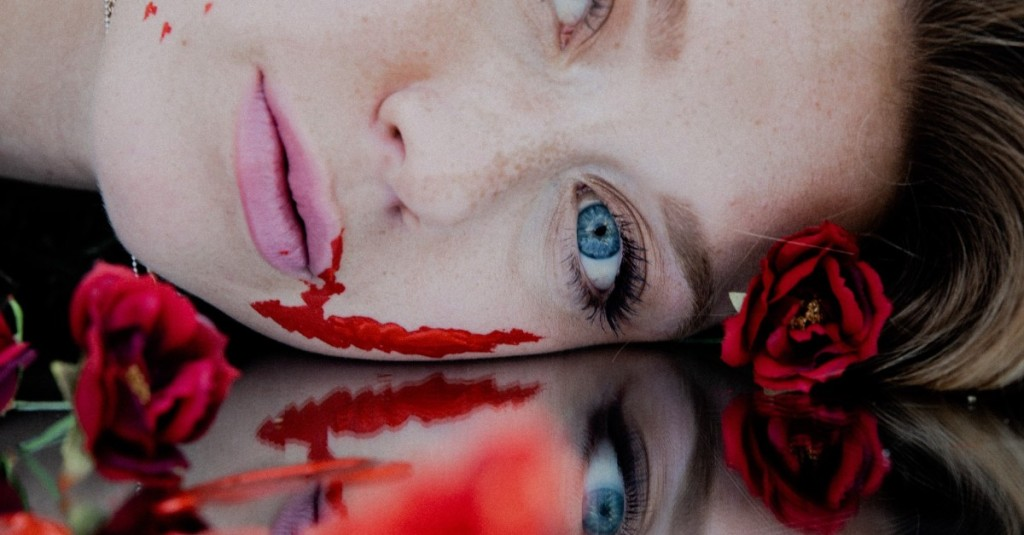 The close up of a dead woman's bloody face lying face down