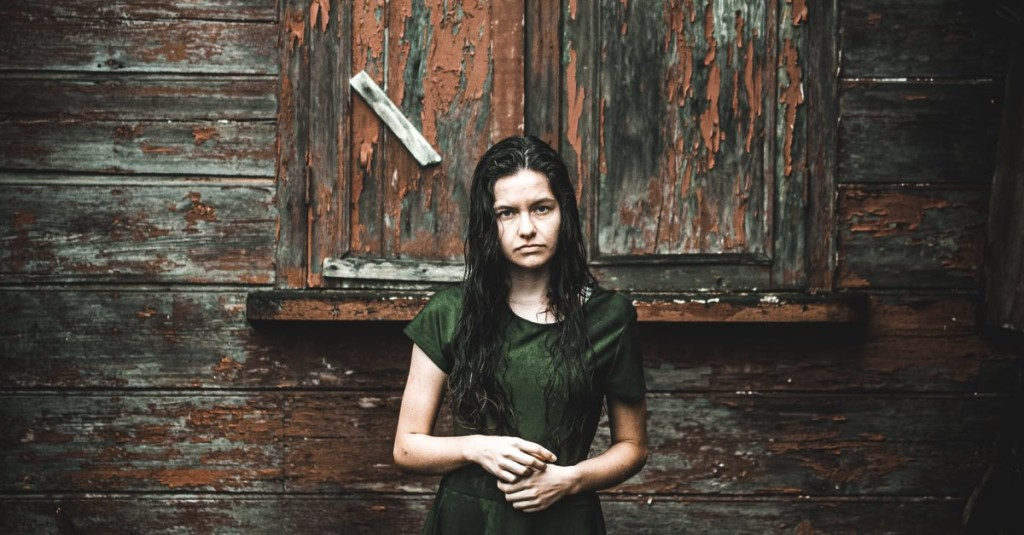 A troubled and sad woman standing in front a rundown building face